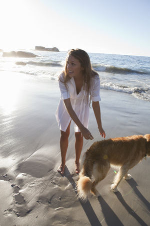 Woman petting dog on beach