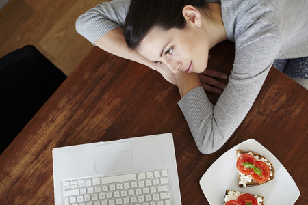 Woman lying on table with laptop