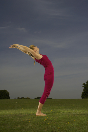 Woman doing yoga in park Stockfoto