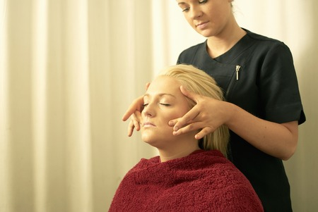 Beautician giving face massage Banque d'images