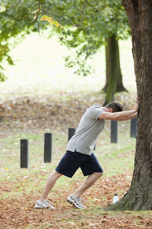 Man stretching for a workout in the park Stock Photo