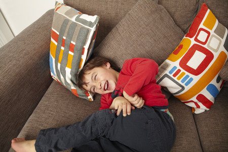 Young boy laughing on sofa 스톡 콘텐츠