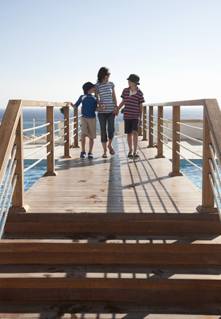 Mother and two sons on boardwalk