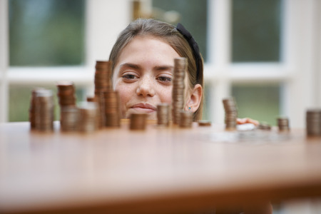 front desk: Girl looking at piles of money Stock Photo