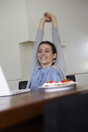 front desk: Woman stretching in front of laptop