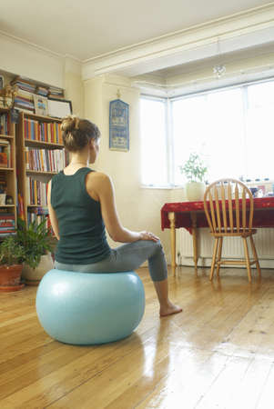 Woman sitting on swiss ball at home