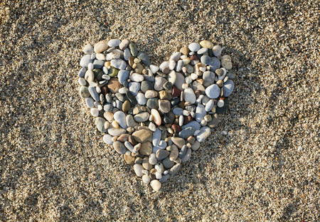 Heart made of pebbles on beach