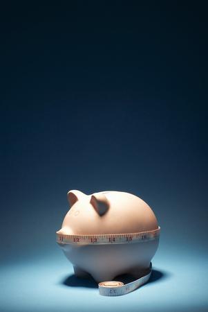 Measuring tape around piggy bank Stock Photo
