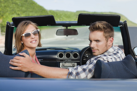 Couple riding in convertible Imagens