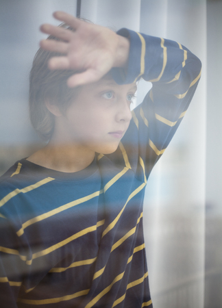 Boy looking through glass of window Banco de Imagens