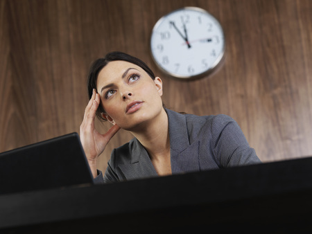 Business woman sitting at desk thinking