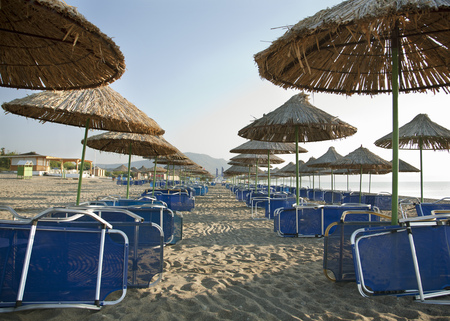 Parasols and sunloungers on beach Stock Photo