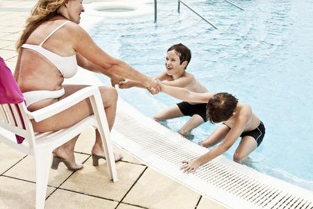 2 boys coaxing grandmother into pool Standard-Bild