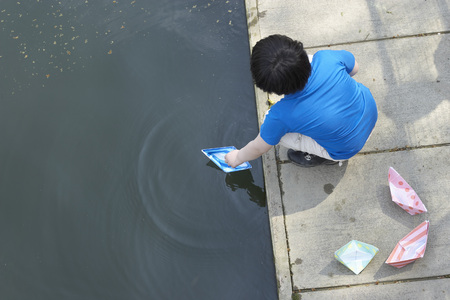 adventuresome: Boy playing with paper sailboats in pond