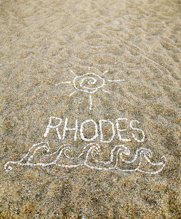 Pebbles on beach spelling Rhodes