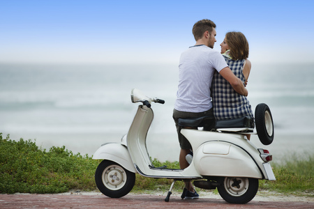 Couple sitting on scooter together Stock Photo