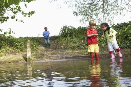 Children in rainboots playing in pond Imagens