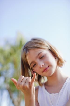 Girl inspecting dragonfly on her finger