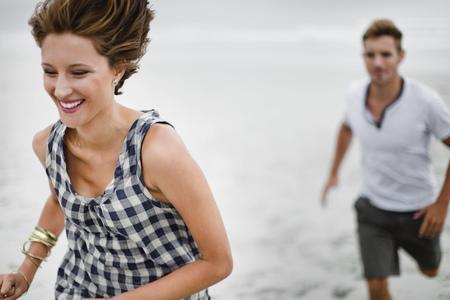 Paar achtervolgen elkaar op het strand