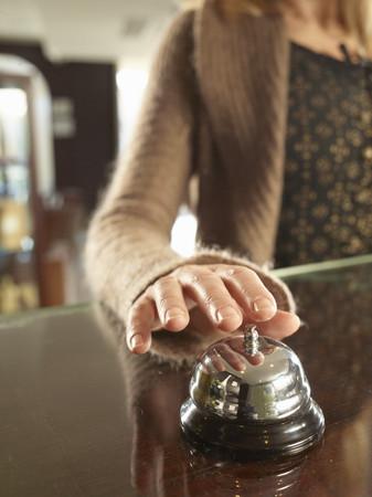 Close up of woman ringin a hotel porters bell Banco de Imagens