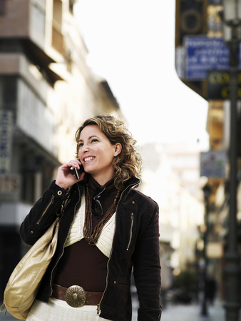 Young woman standing in street using mobile phone, smiling Stock Photo