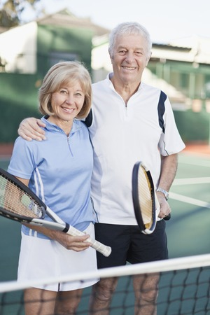 Older couple standing on tennis court