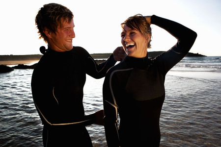 Man zipping up laughing womans wetsuit.