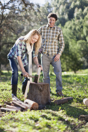 Woman chopping wood outdoors