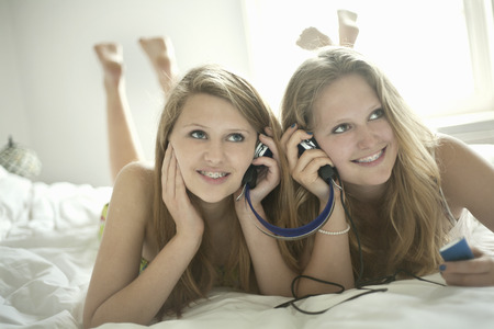 Girls listening to headphones on bed