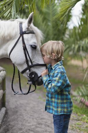 trusted: Boy kissing horse in yard
