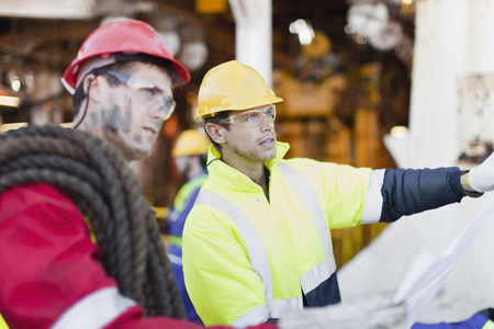 Workers examining blueprints on oil rig