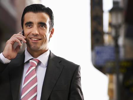 Young businessman using mobile phone in street, smiling