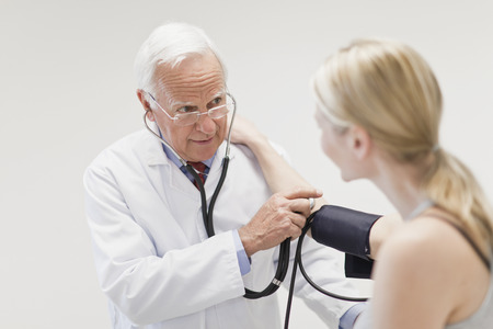 trusted: Doctor taking patient's blood pressure