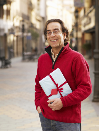 Mature man standing in street holding gift, smiling, portrait