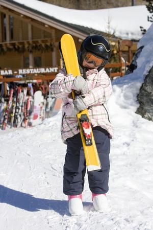 Girl holding skis Banco de Imagens