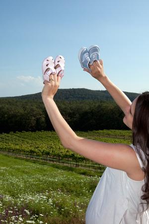 Pregnant woman examining baby shoes Stock Photo
