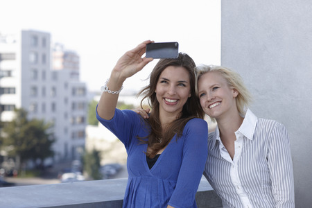 gratified: Women taking picture on balcony Stock Photo