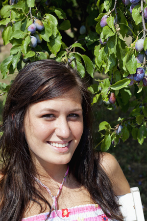 gratified: Woman smiling by fruit tree
