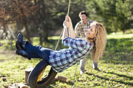 Man pushing girlfriend on tire swing