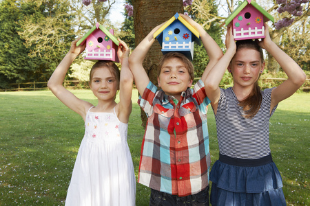 Children holding birdhouses in backyard Stock Photo