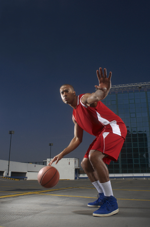 Basketball player dribbling on rooftop Banco de Imagens - 86035644