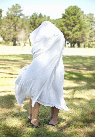 Couple wrapped in towel in park Stock Photo