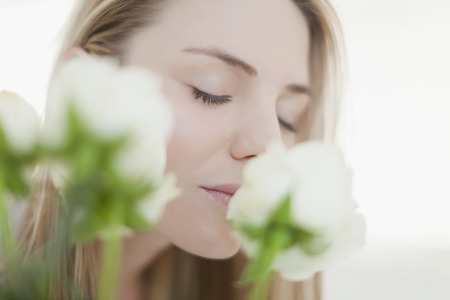 Close up of woman smelling flowers Stock Photo