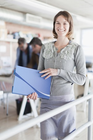 Businesswoman carrying folder in office