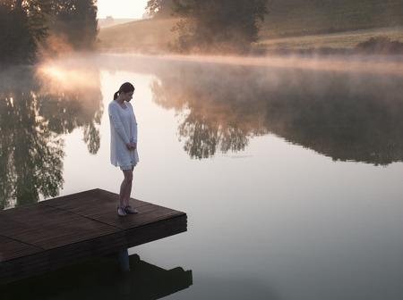 Woman standing on dock of lake