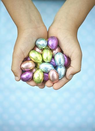 Child holding chocolate eggs Фото со стока