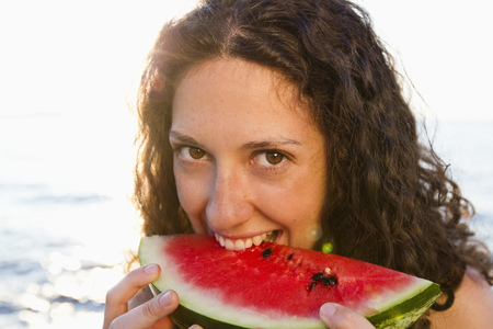 Smiling woman eating watermelon Stock Photo