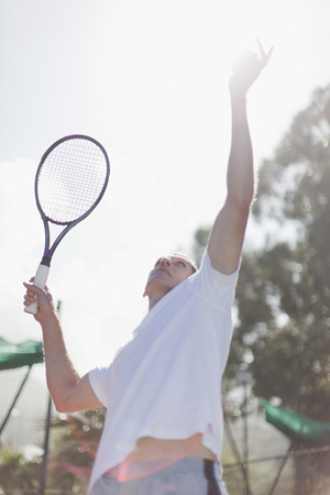 Older man serving tennis ball Banco de Imagens - 85899859