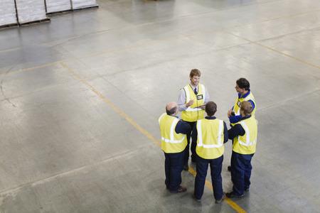 Workers talking in warehouse 版權商用圖片