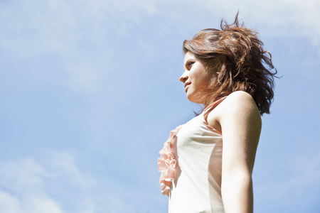 Teenage girl against blue sky Stock Photo
